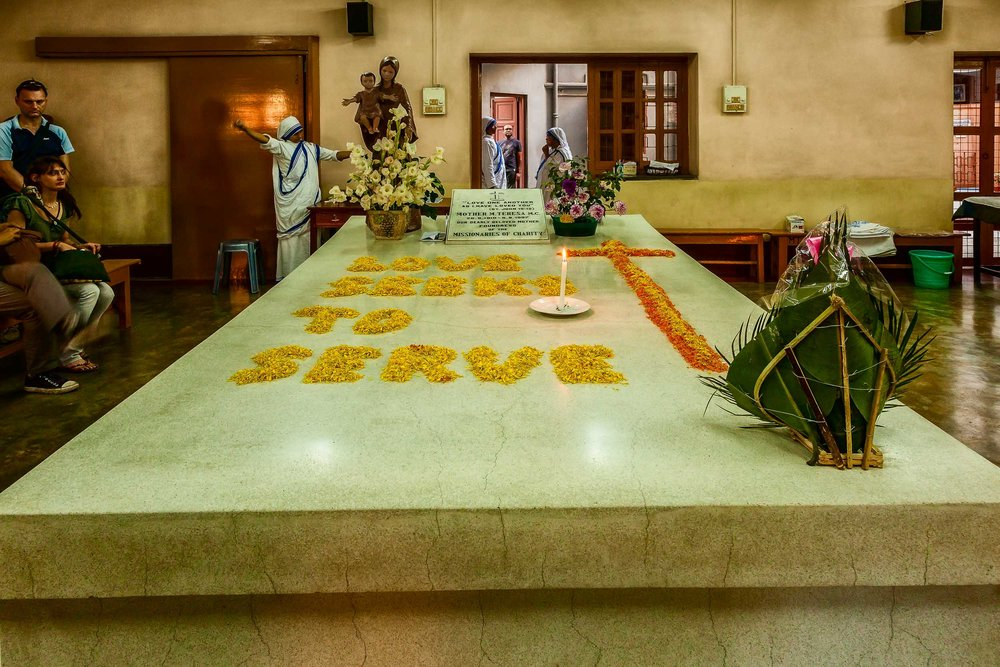"""The tomb of    Mother Teresa    in    Kolkata, India    decorated with fower petals that read    """"Love Seeks To Serve""""   ."""