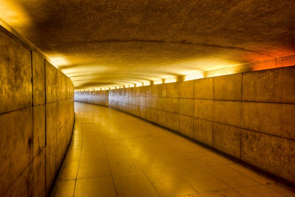 Warm artificial light    illuminates a    pedestrian subway    in    Paris, France   .