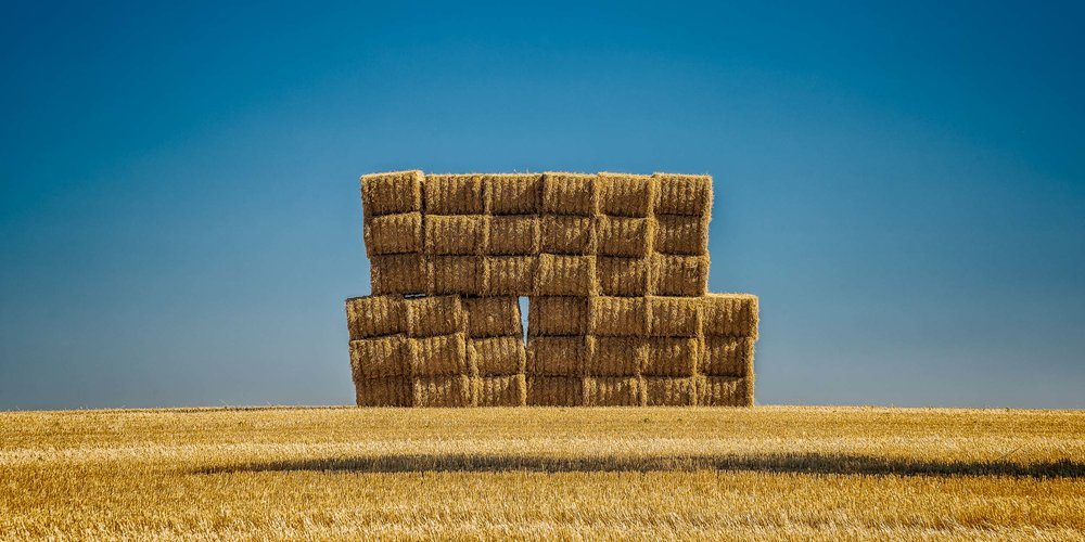 Golden light    illuminates a large stack of    hay bales    near the town of    Byaduk    in Western Victoria,    Australia   .