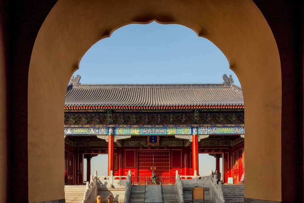 An archway frames one of the magnificently decorated buildings at the Temple Of Heaven in Beijing, China.