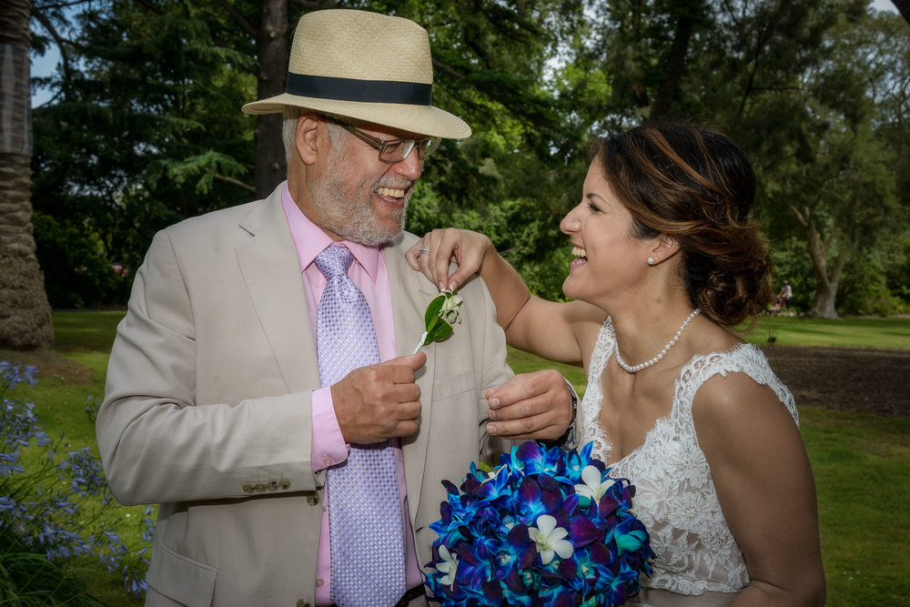 A    candid photo    of a    bride with her father    at a lovely outdoor setting immediately following the wedding service.