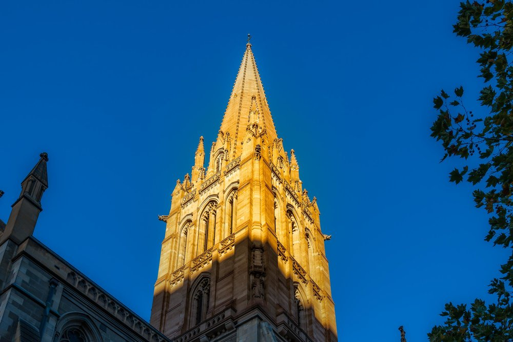 Sunlight spire    set against a blue sky at    St. Paul's Cathedral   ,    Melbourne  .