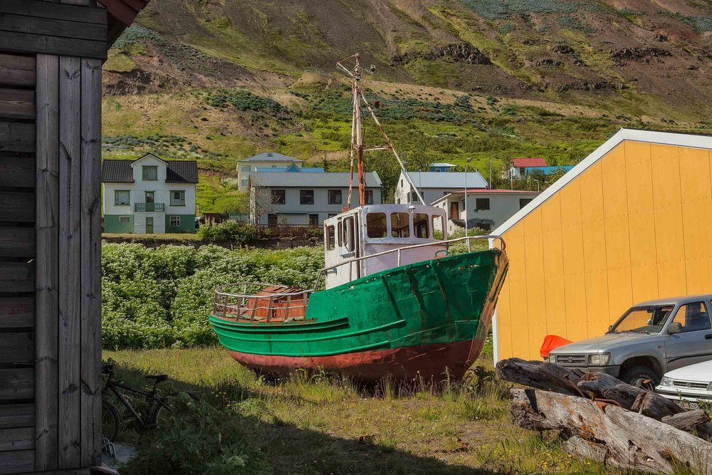 A    green and red       fishing boat    in a yard in the town of    Siglufjordur    in    northern Iceland   .