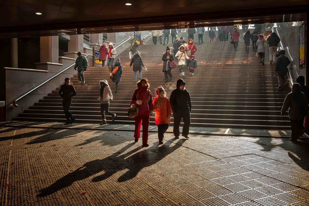 A    family    make their way into a    subway    on a cold    winter's day    in    Harbin, China   .