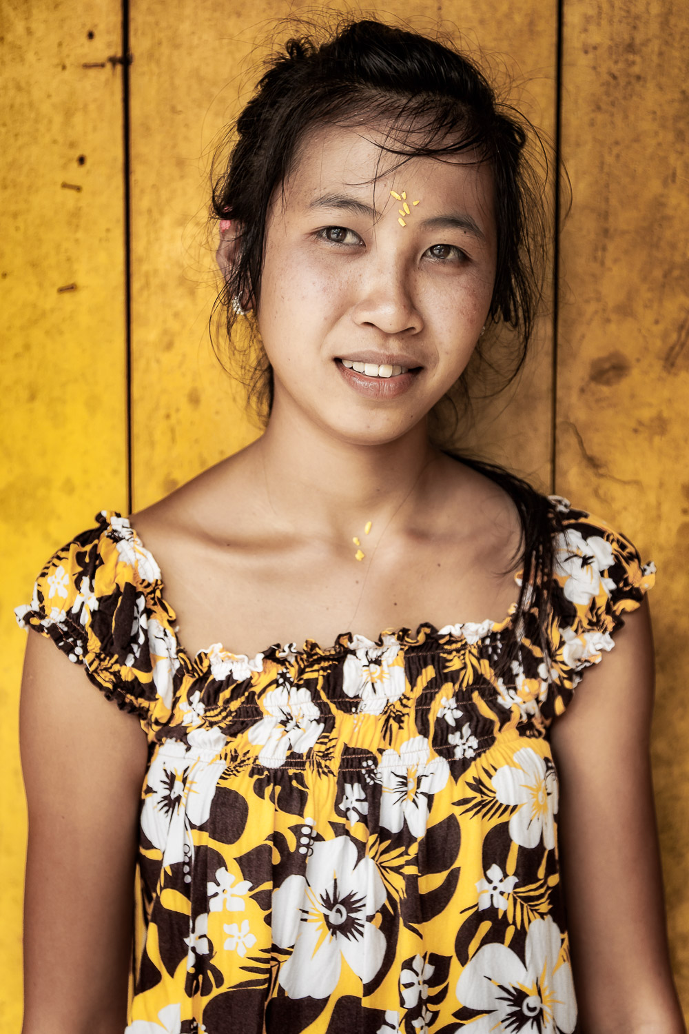 A    young Balinese woman    dressed in yellow and standing against a yellow painted wall in rural    Bali, Indonesia   .