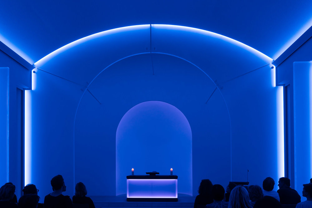 The interior of a chapel, illuminated with    bluish light   , made for a very tranquil and    contemplative scene    in a cemetery in    Berlin, Germany   .