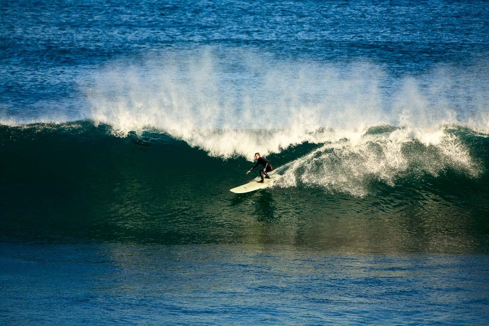 A    surfer    on an early morning surf at the famous    Bells Beach    along the    Great Ocean Road    in    Australia   .