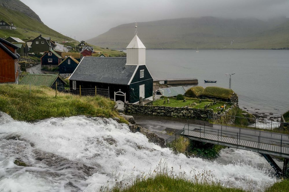 A waterfall cascades past a church and into the sea in the village of    Bøur    on    Vagar,       Faroe Islands   .