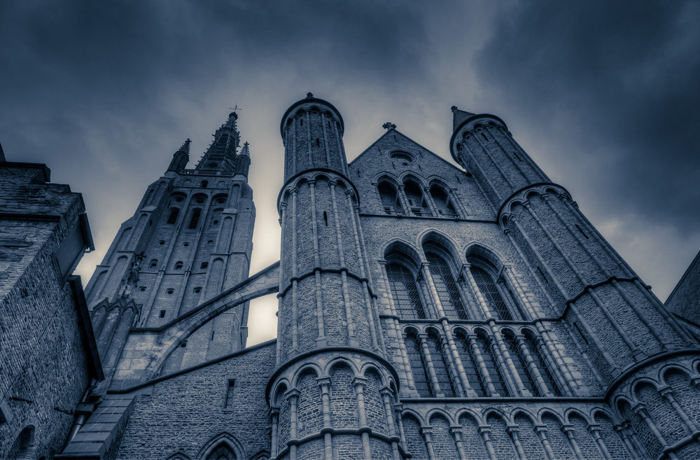 A dramatic exterior view of the    Church Of Our Lady    in    Bruges, Belgium   . This version of the image features a heavy    bluish tint   , which I've added for mood.