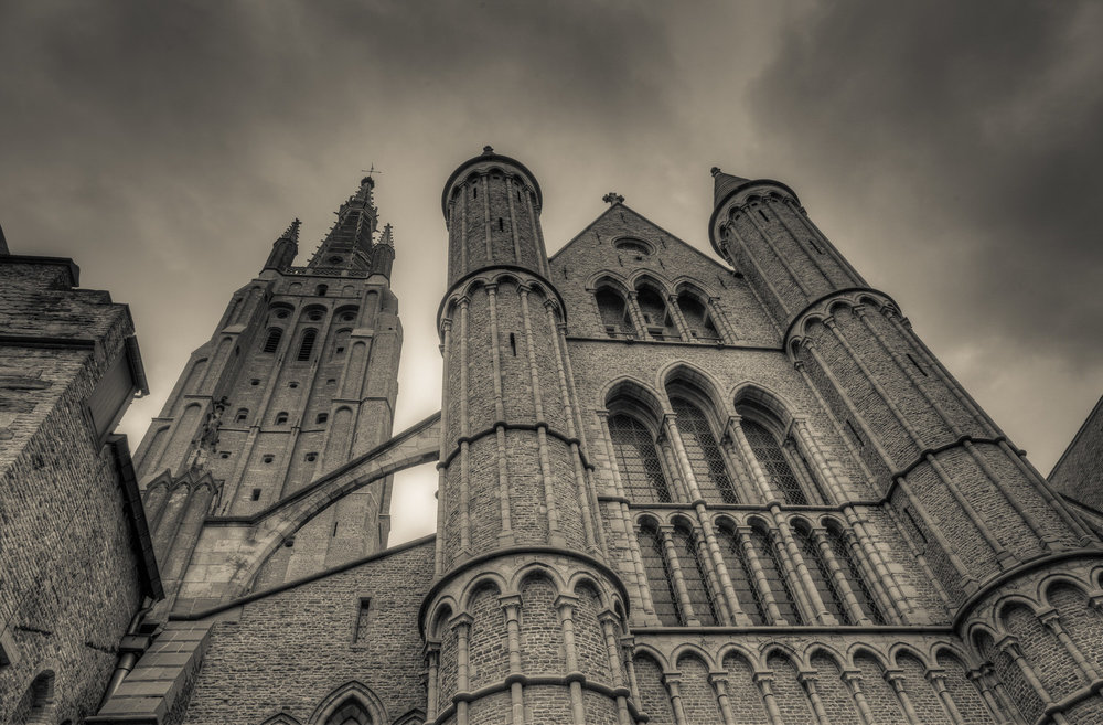 A dramatic exterior view of the  Church Of Our Lady  in  Bruges, Belgium . This version of the image features a  black and white  rendering with a  warm tone  added to the highlights.