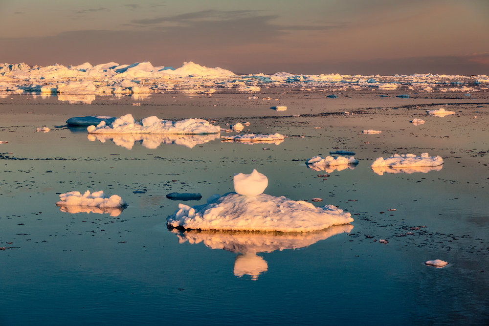 The spectacular colors of the    midnight sun    illuminating icebergs in the    Ilulissat Icefjord, Greenland   .