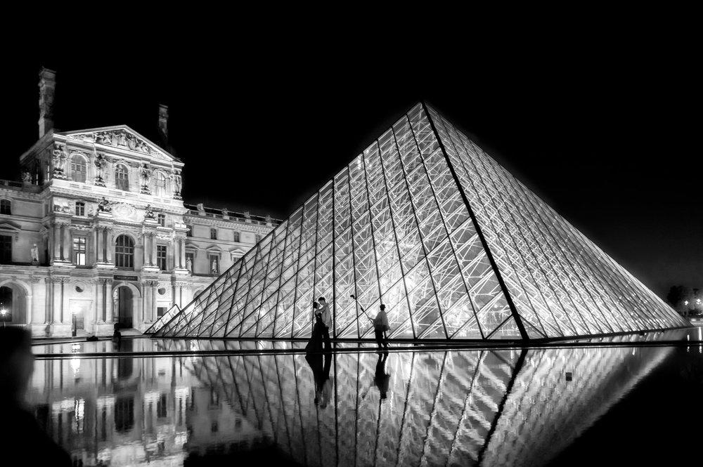Lovers posing for photos, backed by the    Louvre Pyramid   , in    Paris    on a balmy summer's evening.