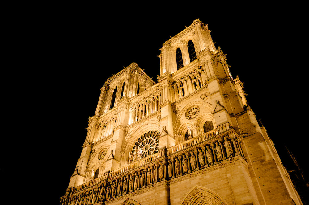 The facade of the magnificent    Notre Dame Cathedral   , bathed in warm light, in    Paris at night   .