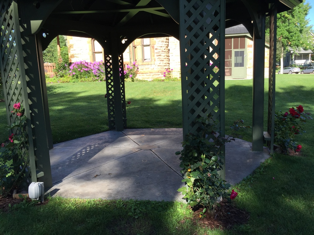 A summertime view of the restored gazebo, complete with heirloom roses in bloom. The dedication plaque is visible in the center of the gazebo floor.