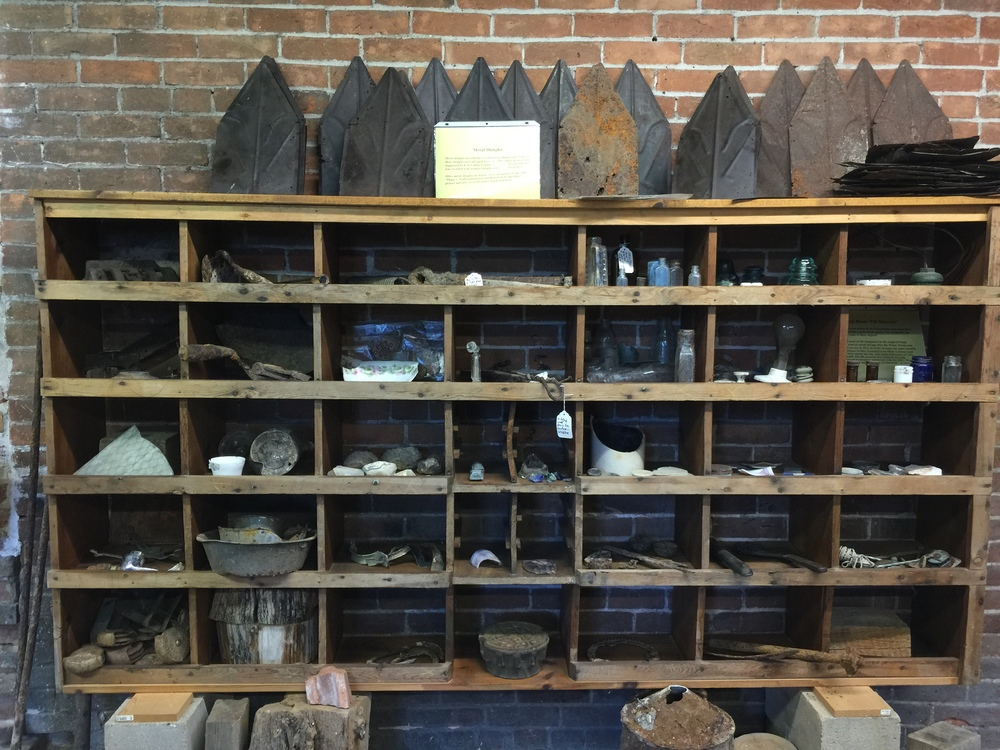 Some original metal shingles were salvaged and restored and are displayed on top of these shelves. The shelves also contain other artifacts recovered from the site during restoration/conservation efforts.