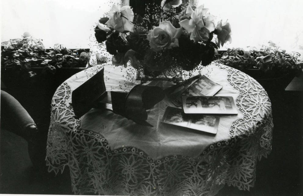 Black and white photograph of the interior of the Avery House located at 328 West Mountain Avenue; Fort Collins, Colorado. This photo shows a small circular table with a lace table cloth and a bouquet of flowers in the center with photos surrounding it.