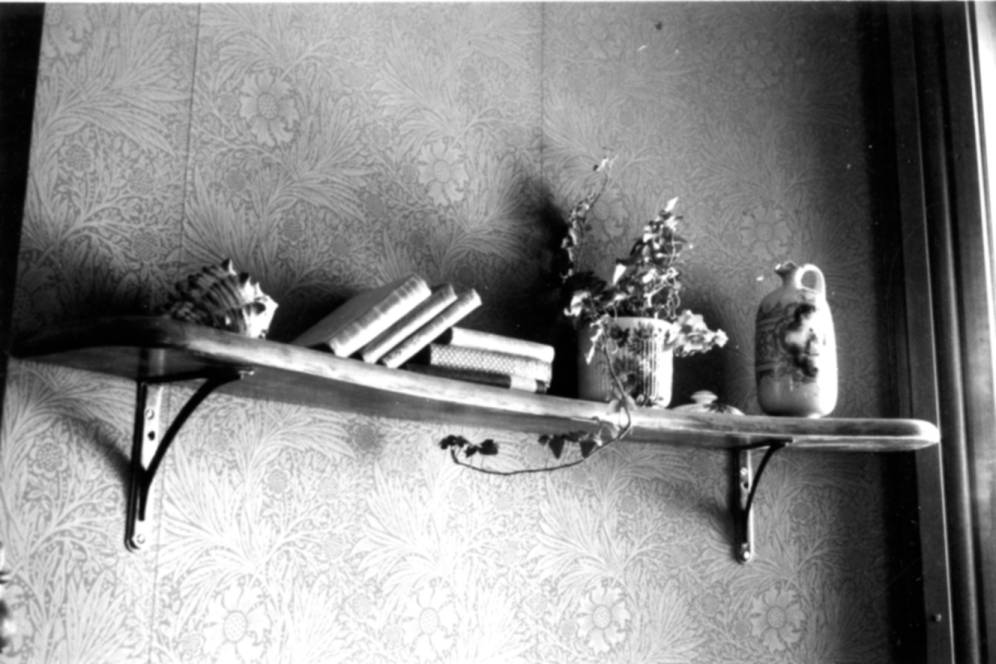 Circa 1980. Black and white photograph of the interior of the Avery House located at 328 West Mountain Avenue; Fort Collins, Colorado.This photo shows a small book shelf/ledge with a few books and a few decorations on it.