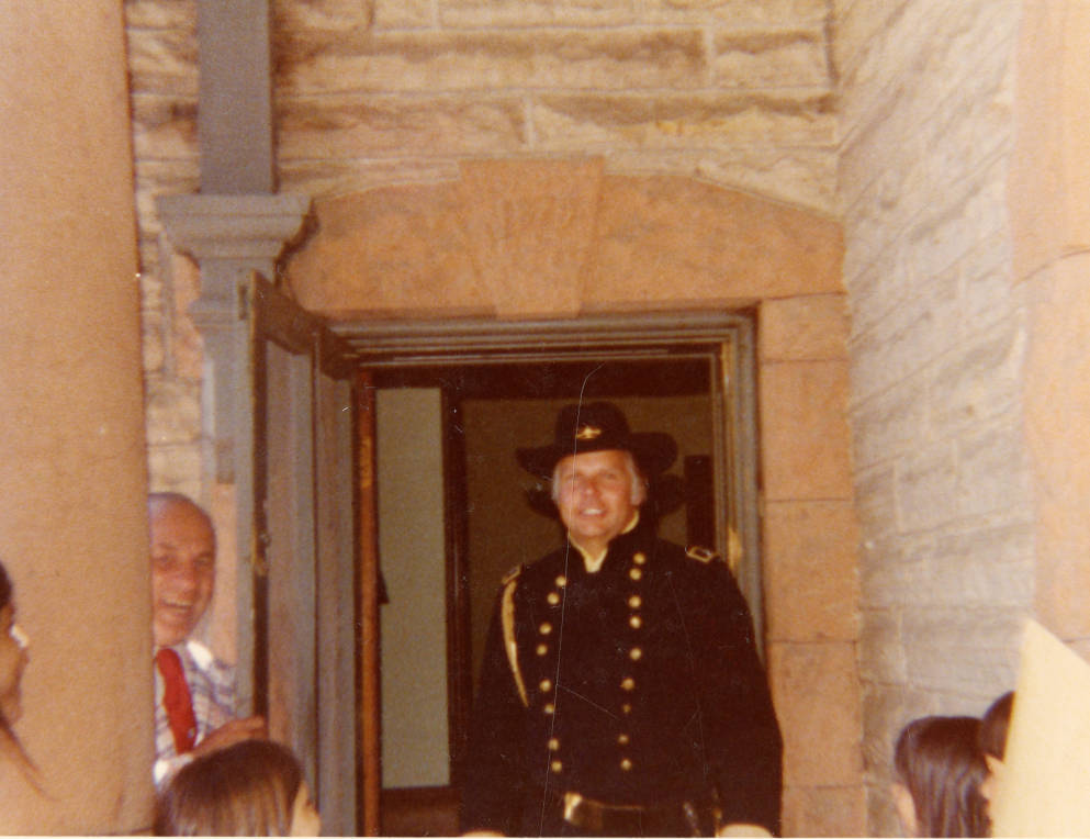 1976 - Color photograph of the dedication ceremony taking place in front of the Avery House located at 328 West Mountain Avenue; Fort Collins, Colorado. The focus of the photograph shows 7 boys dressed in uniforms.