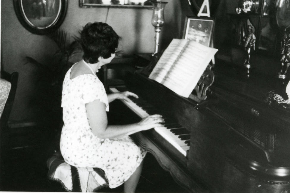 Circa 1980 - Black and white photograph of the interior of the Avery House with June Bennett playing the piano; 328 West Mountain Avenue; Fort Collins, Colorado.