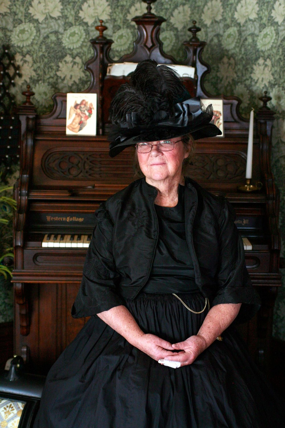 A volunteer docent sits at the organ in the Avery House