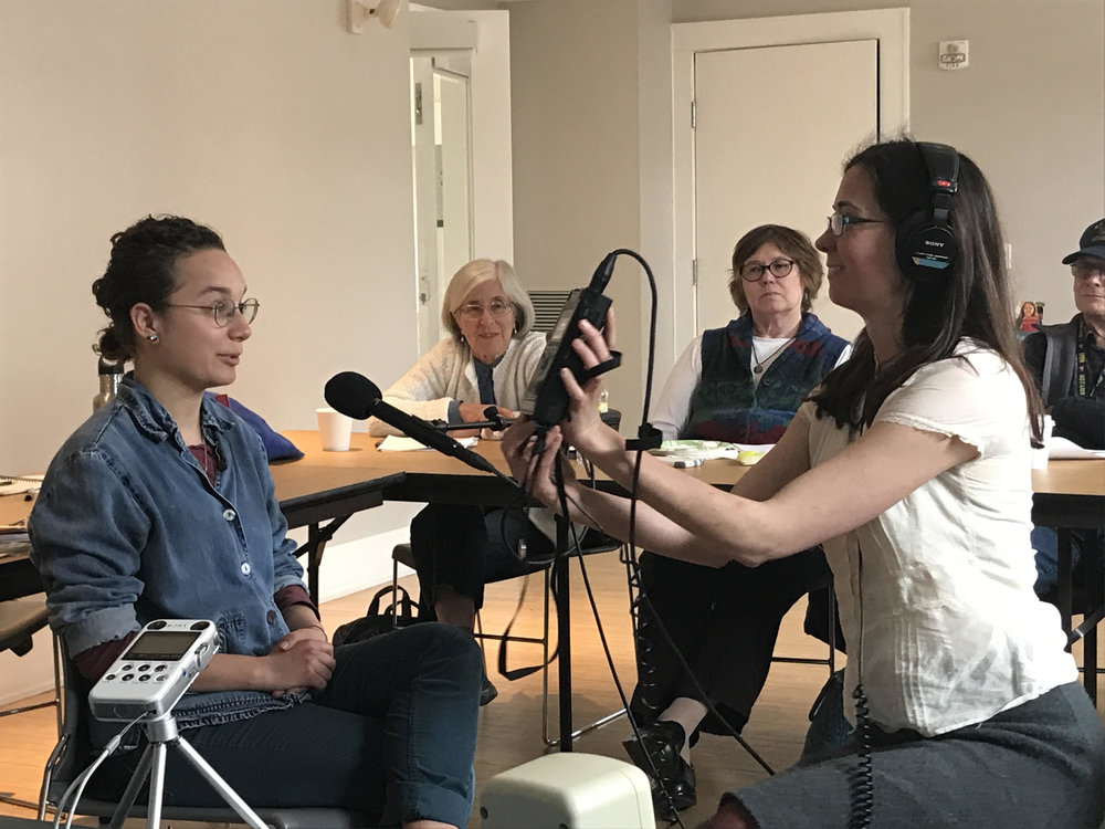 Meghan (right) shows the class how to check their audio levels with Eloise Schultz (left) as the test interviewee. Photo by Tim Garrity.