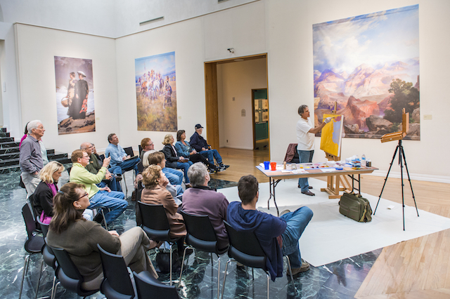 Painting demonstration surrounded by large reproductions of the Masters, photo courtesy of Gilcrease Museum