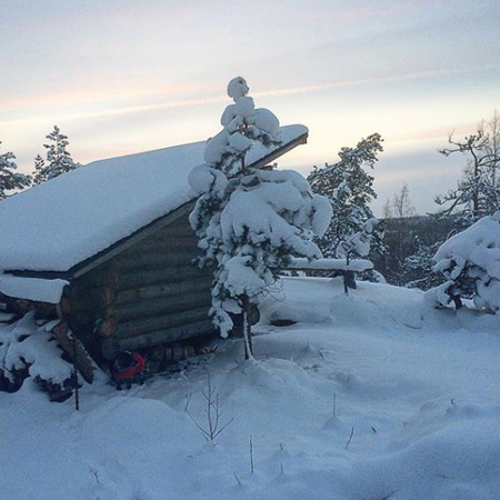 Log shelter in winter landscape, Finnish nature, Råmossa Lodge