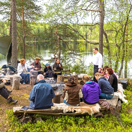 Group of people having a meal in nature, Finnish nature, Råmossa Lodge