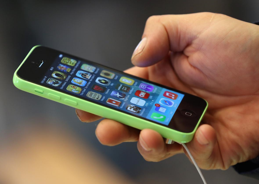Smartphones like the iPhone 5C have been developed for and marketed to upwardly mobile professionals, but increasingly, low-income consumers are using them too. Sean Gallup/Getty Images