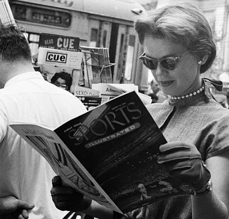 A woman examines the first edition of Sports Illustrated in August 1954, at a location on the tour route.