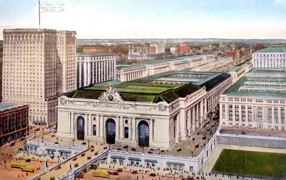 Depictions of the Biltmore Hotel (with flag) and Grand Central Terminal (center front) appear on a postcard from 1913, the year both structures were opened. Vanderbilt Avenue is the road between the two buildings.