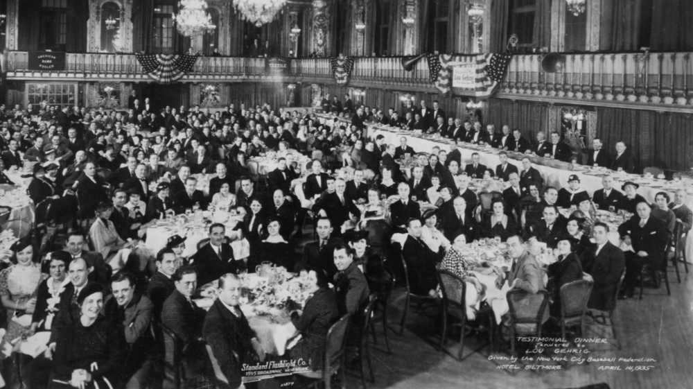 "The Gehrig dinner, with Gehrig standing under an American flag to the left of 12 men seated at the long table. The banner to the right of the flag that's over Gehrig reads, ""Welcome Iron Man Lou Gehrig New York's Own."""