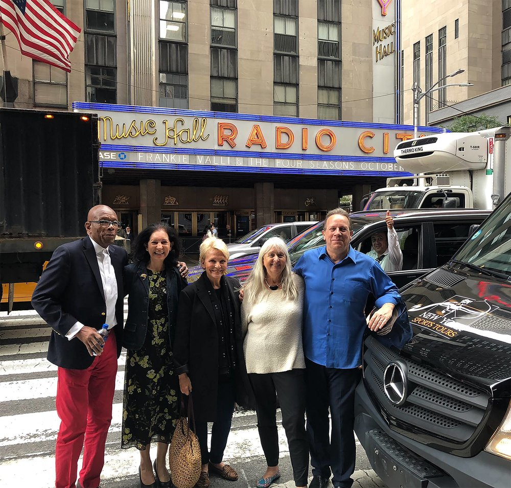 Next to a New York Sports Tours vehicle, Melissa Ludtke (in white) faces the Time & Life Building, where she worked as a reporter for  Sports Illustrated  in 1978. Ludtke joined the tour the day before the 40th anniversary of the landmark Ludtke v. Kuhn federal ruling against Major League Baseball that granted female journalists equal access to players and their stories. Ludtke then served as the post-tour dinner host.