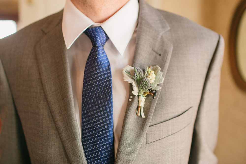 Groomsmen boutonniere of dusty miller, blue thistle, snowberry, and blue virburnum berry wrapped in ivory silk ribbon.