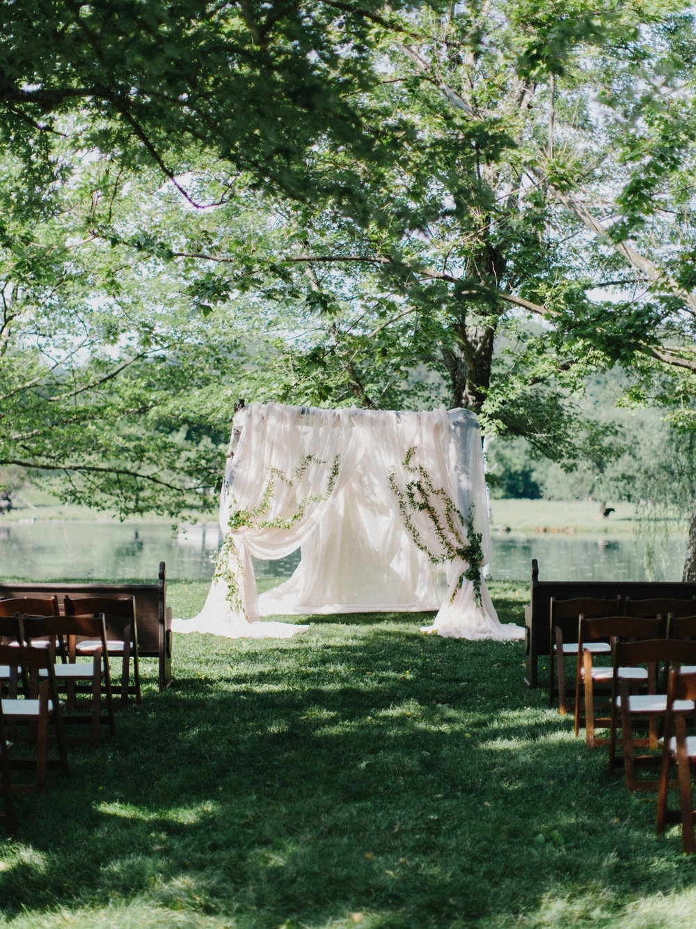 The Ceremony took place under this rustic wooden arch that we draped light apricot drapery on and tied back with vines running up each side.