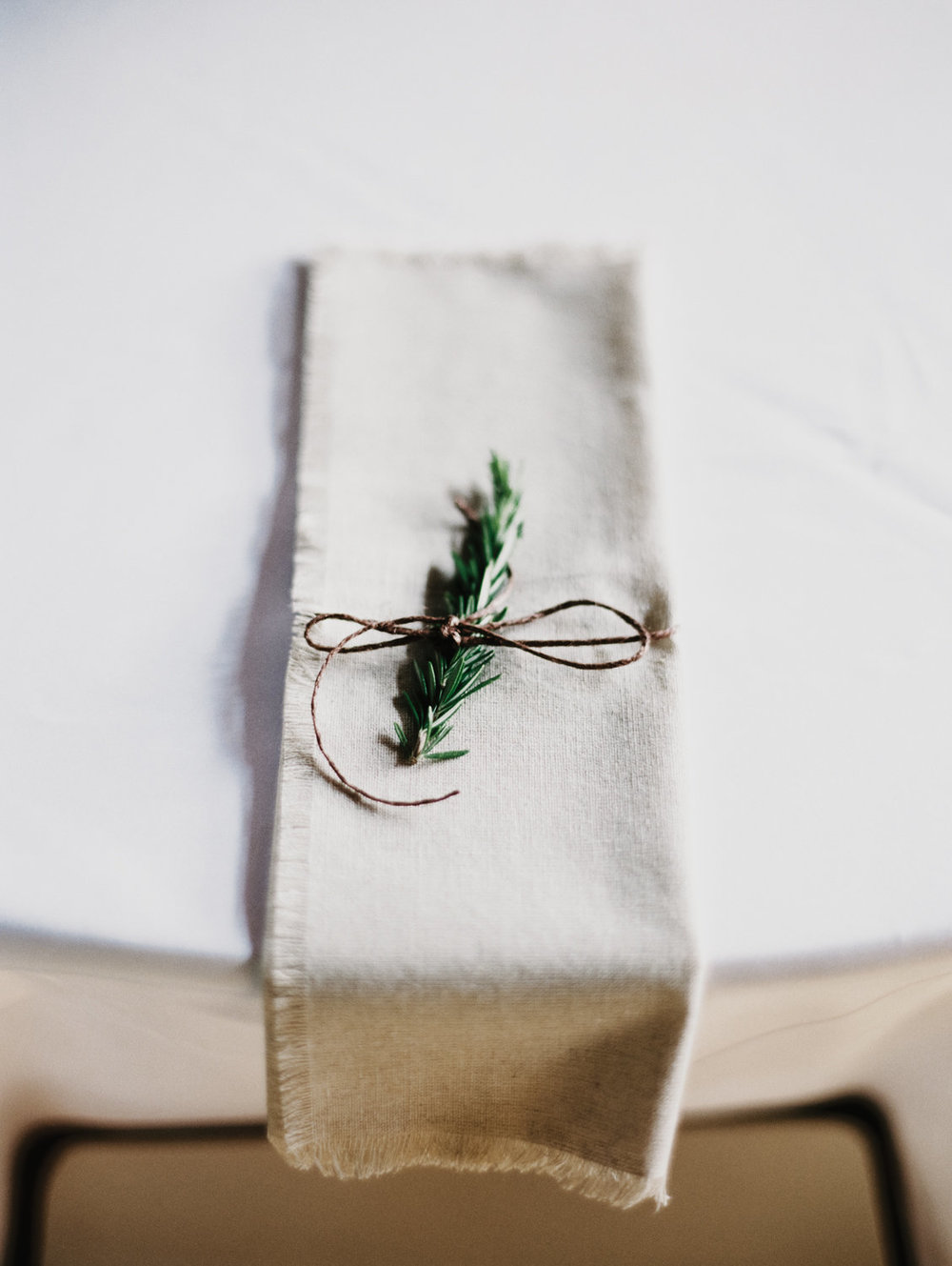 The addition of a Rosemary sprig on each napkin brought the flowers to each guest.