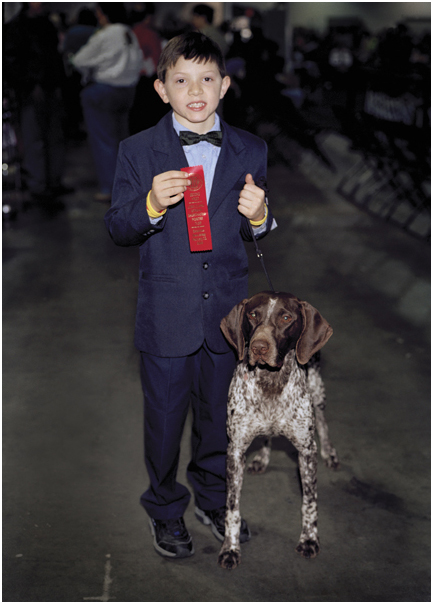 Boy shows ribbon his dog won at American Kennel Club show. East Rutherford, NJ. 2004.