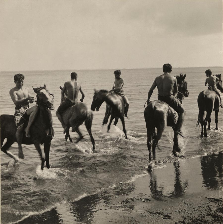 Men on horseback run through the surf in Tahiti, 1922.