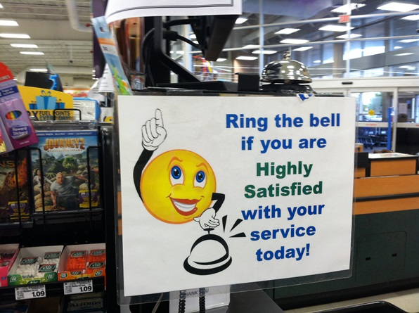 Sign asking supermarket customers to ring a bell if they were highly satisfied with their service.