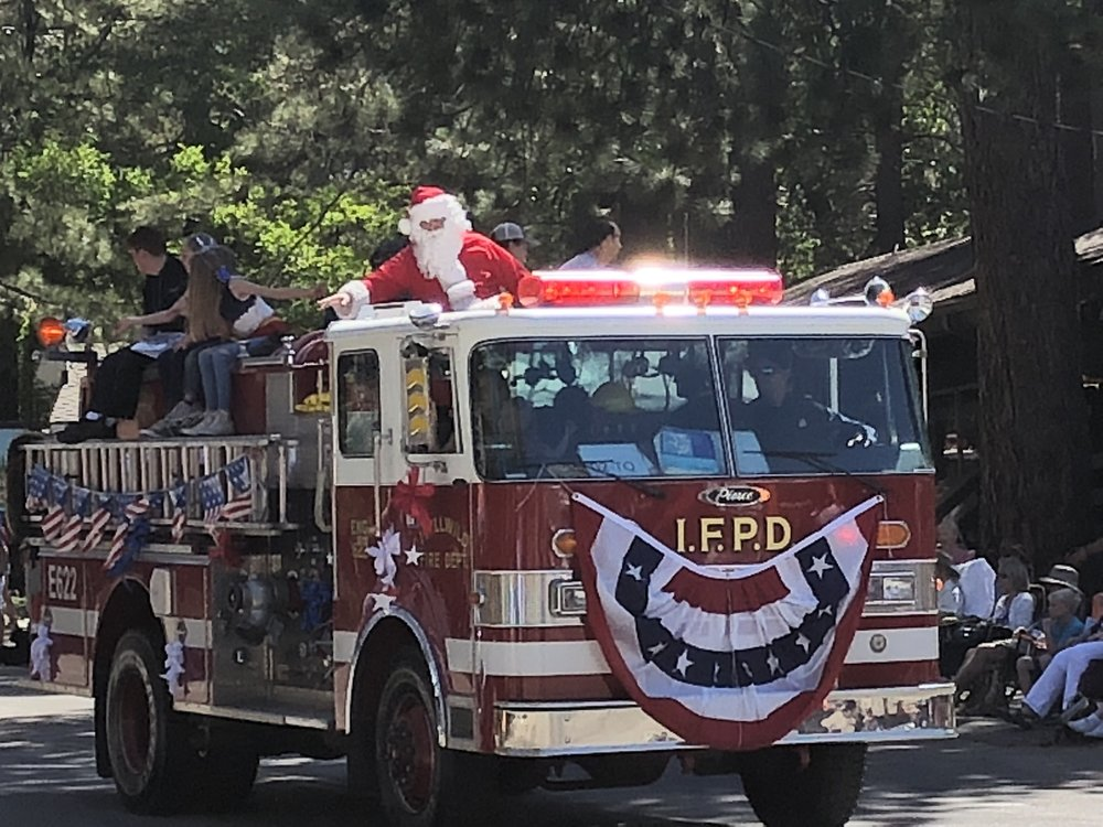 Santa Claus waving from the top of a fire truck in Idyllwild.