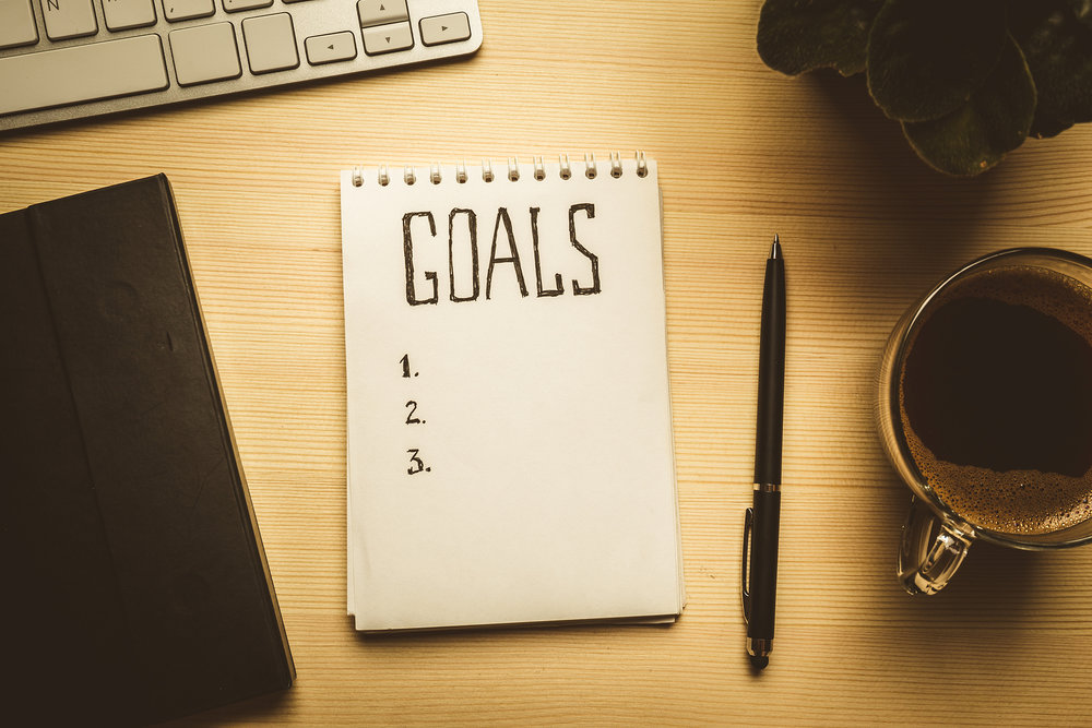 """Notepad and paper with the word """"goals"""" written on it."""