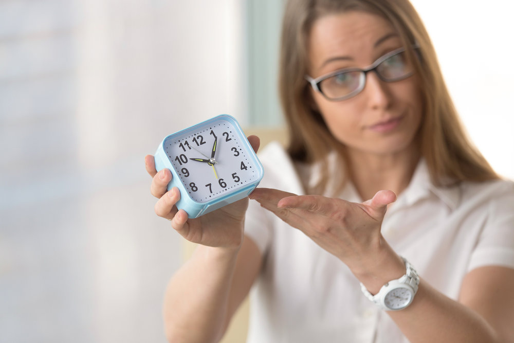 Woman holding up a clock, accusing someone of being late.