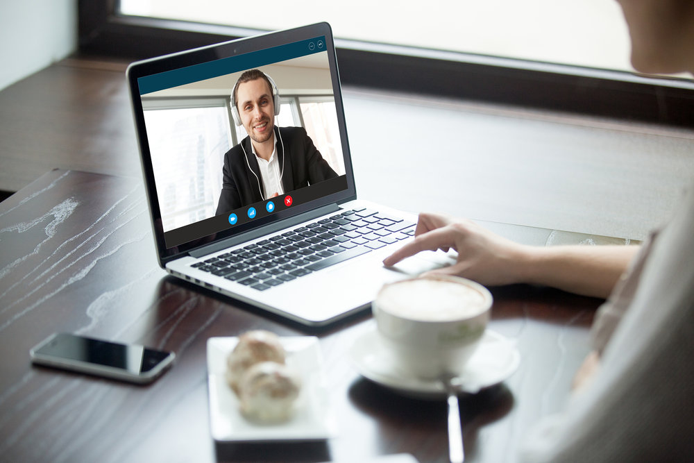 An employee chats with a coworker on a video call.