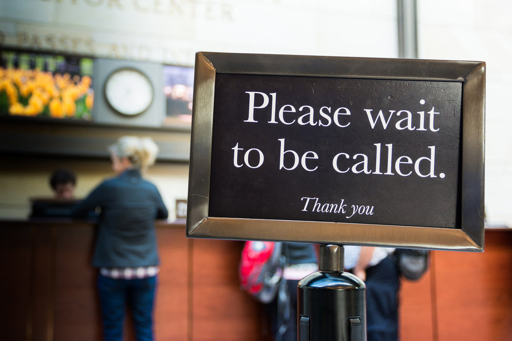 Sign asking customer to wait to be called.