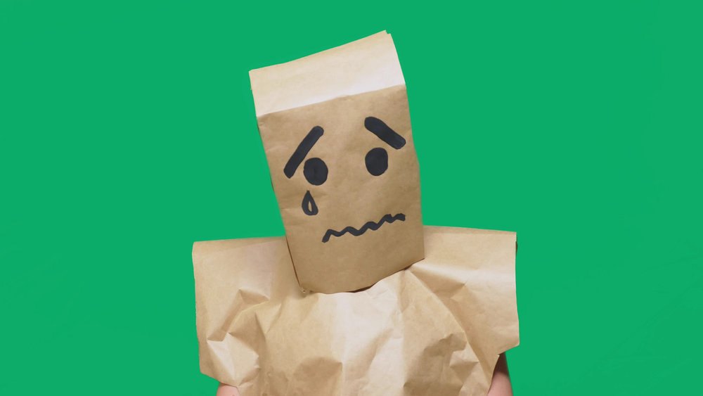 Emotionally exhausted person wearing a paper bag over their head.