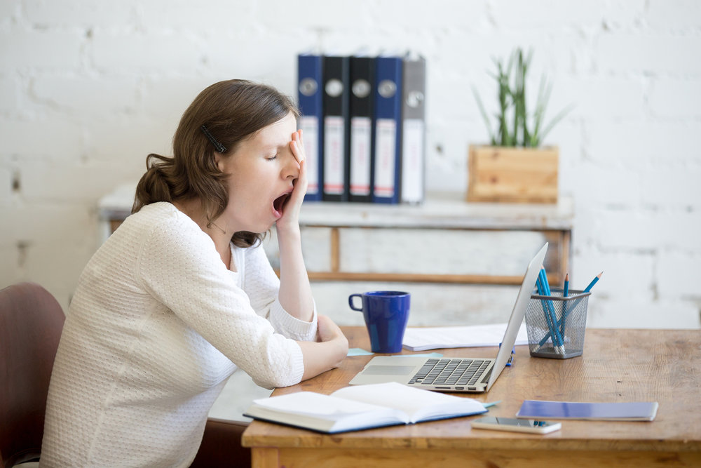 An office worker sitting at her computer, yawning.
