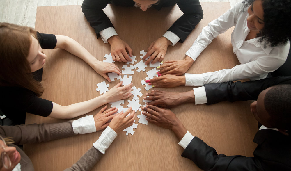 A group of employees try to solve a puzzle together.