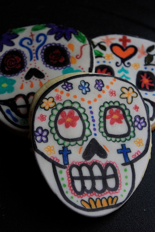 Want to make these super awesome sugar skulls? They're simply sugar cookies, covered in rolled fondant and then decorated by drawing with edible markers.