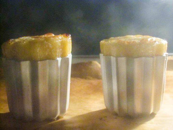 Caneles just beginning to rise in the oven