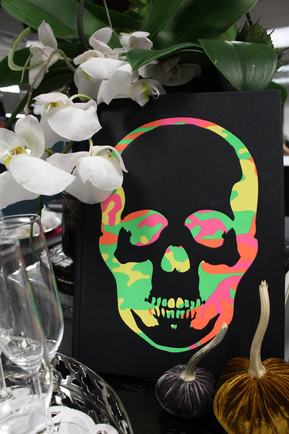 Neon skulls, velvet pumpkins and fresh white orchids provide the perfect party décor